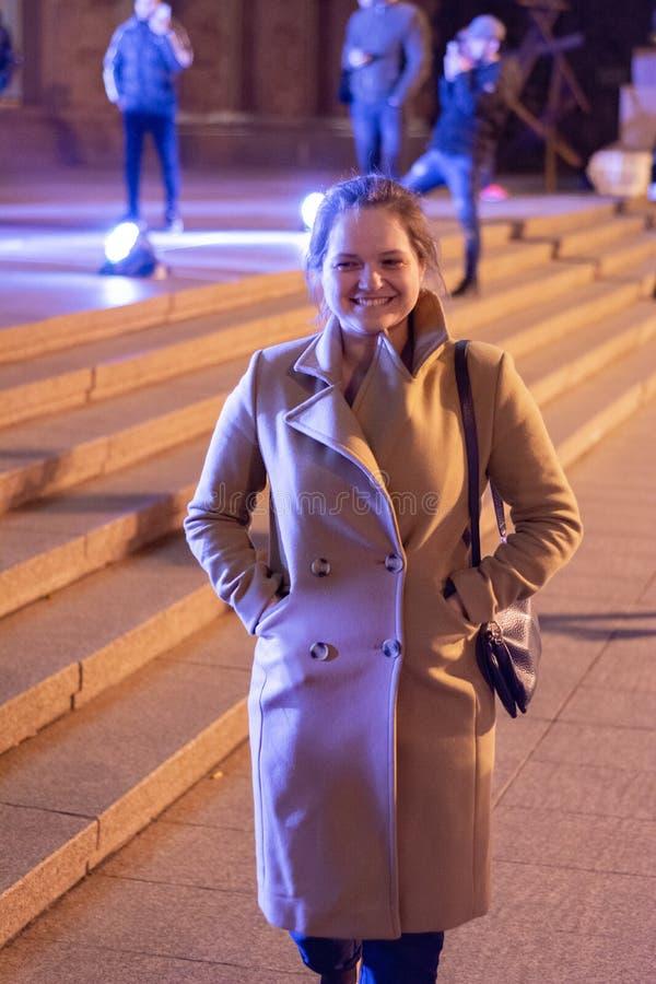 Ένα κορίτσι σε ένα παλτό περπατά μέσω των οδών νύχτας της πόλης κοντά στις προθήκες στοκ εικόνες