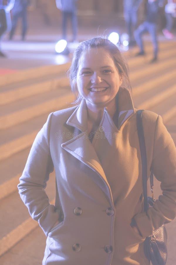 Ένα κορίτσι σε ένα παλτό περπατά μέσω των οδών νύχτας της πόλης κοντά στις προθήκες στοκ εικόνα
