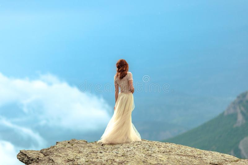 Ένα κορίτσι σε ένα Tulle και το topi περιζώνουν τις στάσεις στη βροχή μεταξύ των βράχων στοκ εικόνα με δικαίωμα ελεύθερης χρήσης