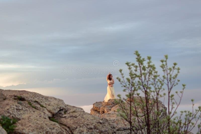 Ένα κορίτσι σε ένα Tulle και το topi περιζώνουν τις στάσεις στη βροχή μεταξύ των βράχων στοκ εικόνα