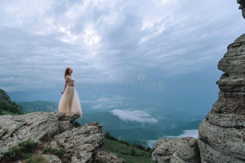 Ένα κορίτσι σε ένα Tulle και το topi περιζώνουν τις στάσεις στη βροχή μεταξύ των βράχων στοκ εικόνες με δικαίωμα ελεύθερης χρήσης