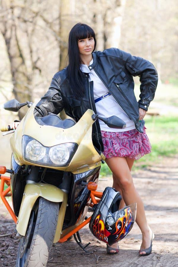 Ένα κορίτσι στέκεται δίπλα σε μια μοτοσικλέτα στοκ εικόνα