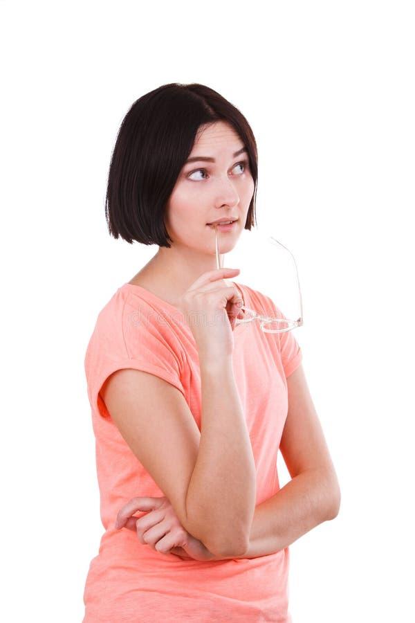 Ένα κορίτσι στέκεται σκεπτικά και τεθειμένα γυαλιά στα χείλια της σε ένα απομονωμένο λευκό υπόβαθρο στοκ εικόνες με δικαίωμα ελεύθερης χρήσης