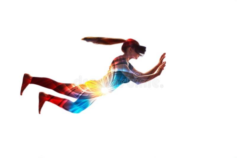 Ένα κορίτσι στα όνειρα γυαλιών εικονικής πραγματικότητας που πετά Έννοια των σύγχρονων τεχνολογιών και των τεχνολογιών στοκ εικόνα