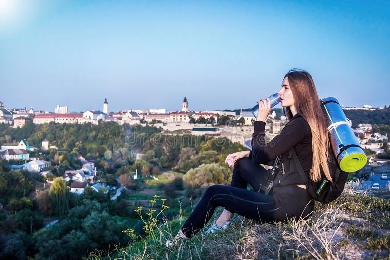 Ένα κορίτσι στο τοπ πίνει το νερό από ένα μπουκάλι στοκ φωτογραφία με δικαίωμα ελεύθερης χρήσης