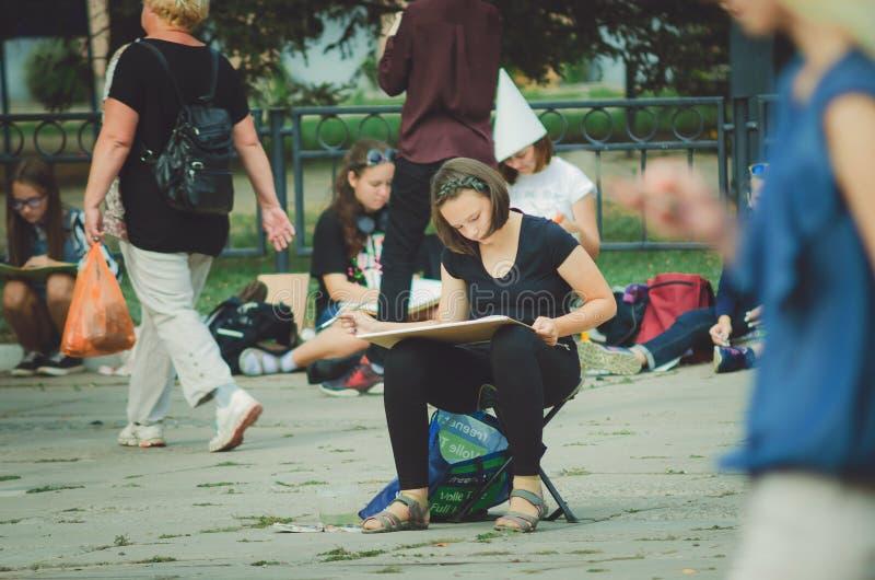 Ένα κορίτσι των σχολικών χρωμάτων τέχνης στο πάρκο πόλεων σε έναν υπαίθριο προς τιμή την ημέρα πόλεων ` s στοκ φωτογραφία