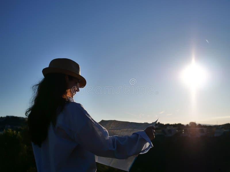 Ένα κορίτσι brunette σε ένα καπέλο εξετάζει έναν χάρτη εκτάσεων ενάντια στον ήλιο αύξησης, copyspace στοκ εικόνα