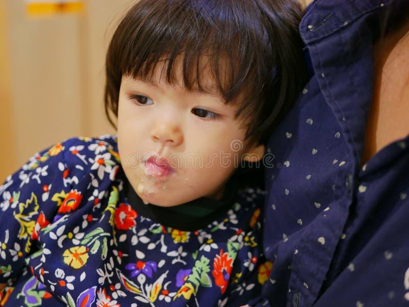 Ένα κοριτσάκι που νιώθει γεμάτο και λυγίζει στη μητέρα της, με το πρόσωπό της να λερώνει με το παγωτό που μόλις έφαγε στοκ φωτογραφία με δικαίωμα ελεύθερης χρήσης