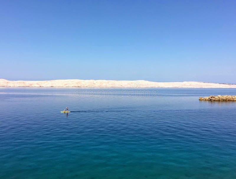 Ένα κουπί προσώπων που επιβιβάζεται στα ήρεμα ανοικτά νερά της αδριατικής θάλασσας κατά μήκος της αδριατικής εθνικής οδού στην Κρ στοκ φωτογραφίες με δικαίωμα ελεύθερης χρήσης