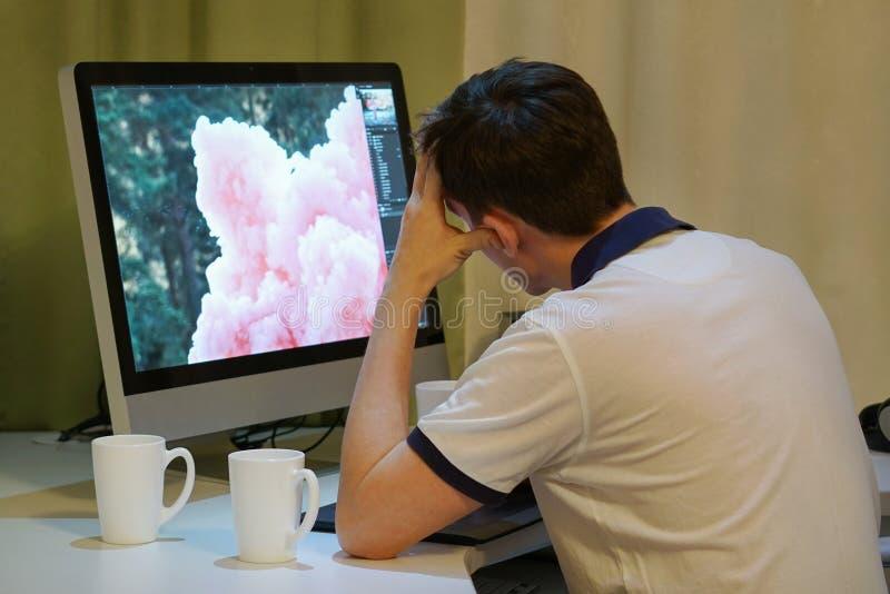 Ένα κουρασμένο ανεξάρτητο retoucher κάθεται μπροστά από το όργανο ελέγχου τη νύχτα στοκ εικόνες