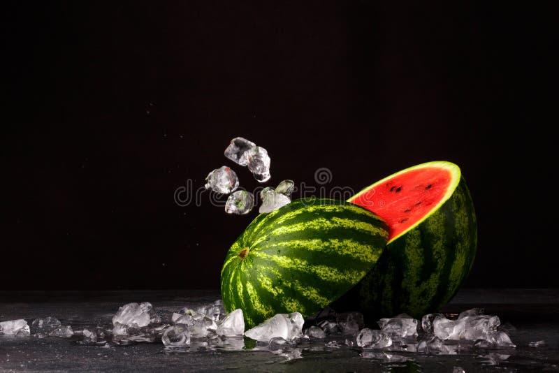 Ένα κόκκινο καρπούζι περικοπών σε ένα μαύρο υπόβαθρο Juicy και φρέσκο καρπούζι δίπλα στους κύβους πάγου Αναζωογονώντας θερινά μού στοκ εικόνες με δικαίωμα ελεύθερης χρήσης