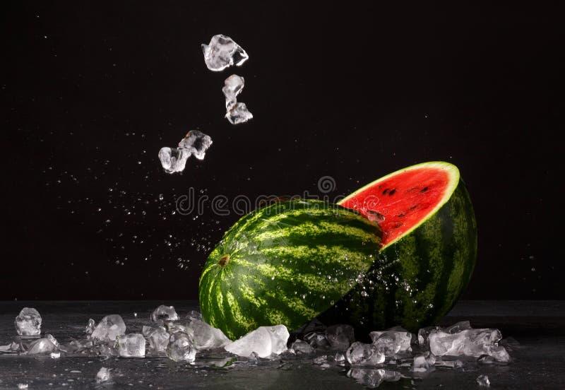 Ένα κόκκινο καρπούζι περικοπών σε ένα μαύρο υπόβαθρο Juicy και φρέσκο καρπούζι δίπλα στους κύβους πάγου Αναζωογονώντας θερινά μού στοκ εικόνα με δικαίωμα ελεύθερης χρήσης