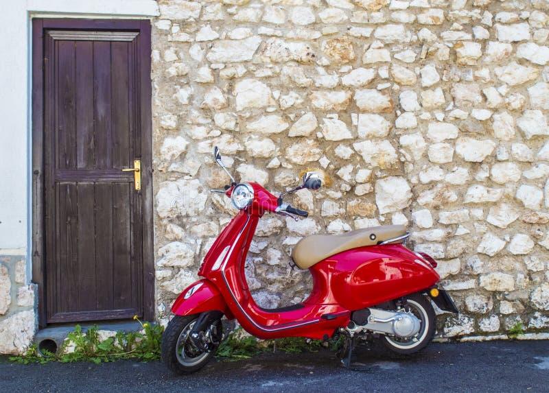 Ένα κόκκινο μηχανικό δίκυκλο μπροστά από ένα παλαιό σπίτι πετρών στοκ εικόνα με δικαίωμα ελεύθερης χρήσης