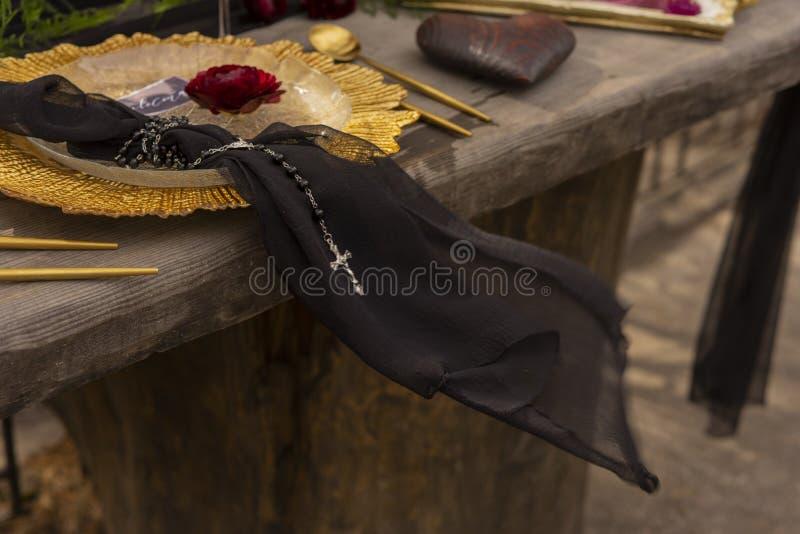 Ένα κόκκινο μπουμπούκι τριαντάφυλλου βάζει σε ένα χρυσό πιάτο δίπλα σε ένα μαύρο πέπλο με το α στοκ εικόνες