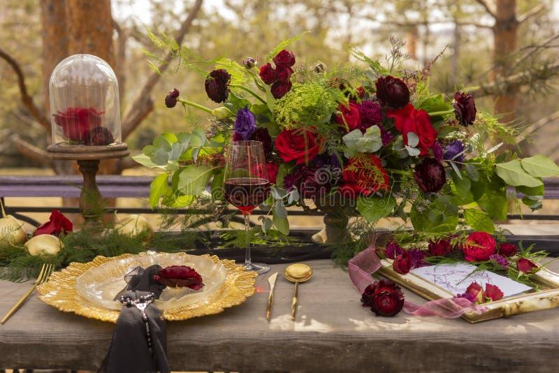 Ένα κόκκινο μπουμπούκι τριαντάφυλλου που βρίσκεται σε μια χρυσή πιατέλα με ένα μαύρο πέπλο, δίπλα στοκ φωτογραφίες