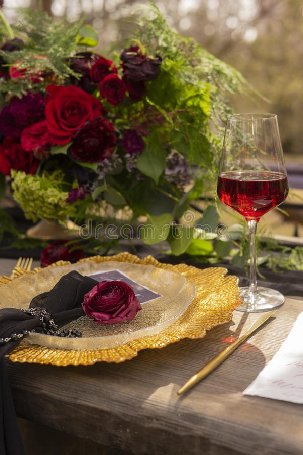Ένα κόκκινο μπουμπούκι τριαντάφυλλου, που βρίσκεται σε μια χρυσή πιατέλα, δίπλα σε ένα γυαλί του κοκκίνου στοκ φωτογραφίες