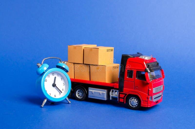 Ένα κόκκινο φορτηγό με τα κουτιά από χαρτόνι και ένα μπλε ξυπνητήρι Εκφράστε την παράδοση στην έννοια λίγος χρόνου Προσωρινή αποθ στοκ φωτογραφία