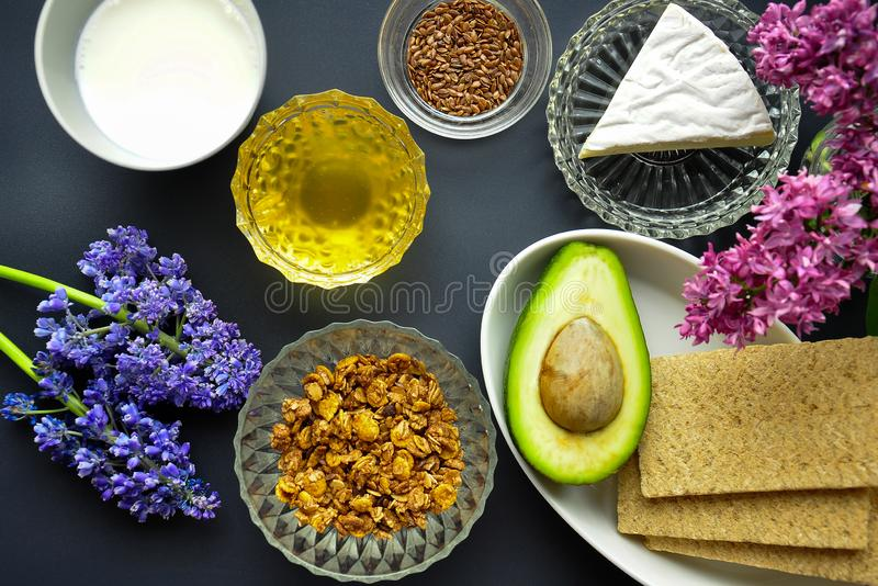 Ένα κύπελλο των δημητριακών με oatmeal και γάλακτος και λιναριού οι σπόροι, μέλι, τυρί, φρυγανιά με το αβοκάντο, τηγανίτα Το υγιέ στοκ εικόνες με δικαίωμα ελεύθερης χρήσης