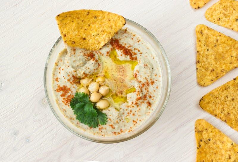Ένα κύπελλο του κρεμώδους hummus με το ελαιόλαδο και τα τσιπ στοκ φωτογραφία με δικαίωμα ελεύθερης χρήσης