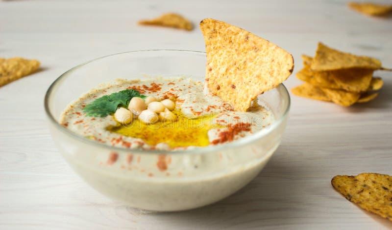 Ένα κύπελλο του κρεμώδους hummus με το ελαιόλαδο και τα τσιπ στοκ εικόνα