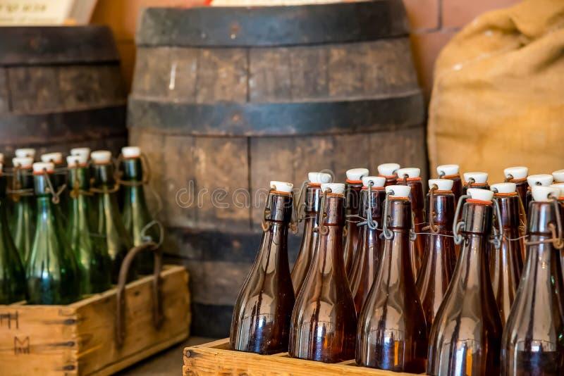 Ένα κλουβί μπουκαλιών που συσσωρεύεται πάνω από ένα ξύλινο βαρέλι σε μια σοφίτα ενός ζυθοποιείου μπύρας στοκ φωτογραφία
