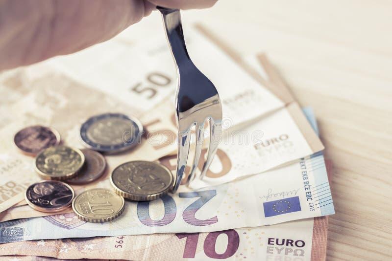 Ένα λαμπρό δίκρανο μετάλλων στηρίχτηκε σε έναν σωρό των ευρο- τραπεζογραμματίων και των νομισμάτων στοκ φωτογραφίες με δικαίωμα ελεύθερης χρήσης