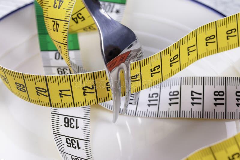 Ένα λαμπρό δίκρανο συντρίβει ένα πολύχρωμο εκατοστόμετρο σε ένα άσπρο πιάτο με μπλε σύνορα στοκ φωτογραφίες