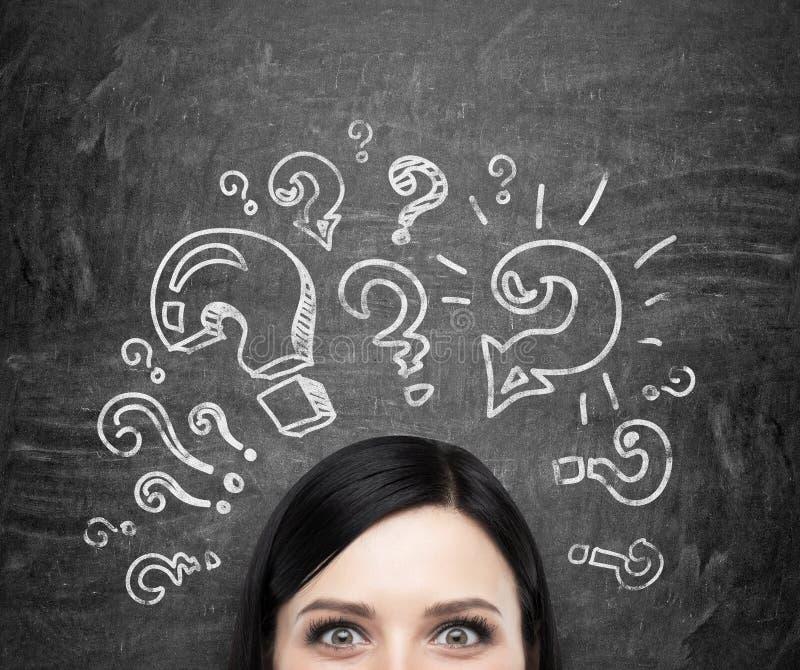 Ένα μέτωπο του κοριτσιού που συλλογίζεται για τα άλυτα προβλήματα Τα ερωτηματικά σύρονται γύρω από το κεφάλι μαύρο chalkboa στοκ φωτογραφία με δικαίωμα ελεύθερης χρήσης