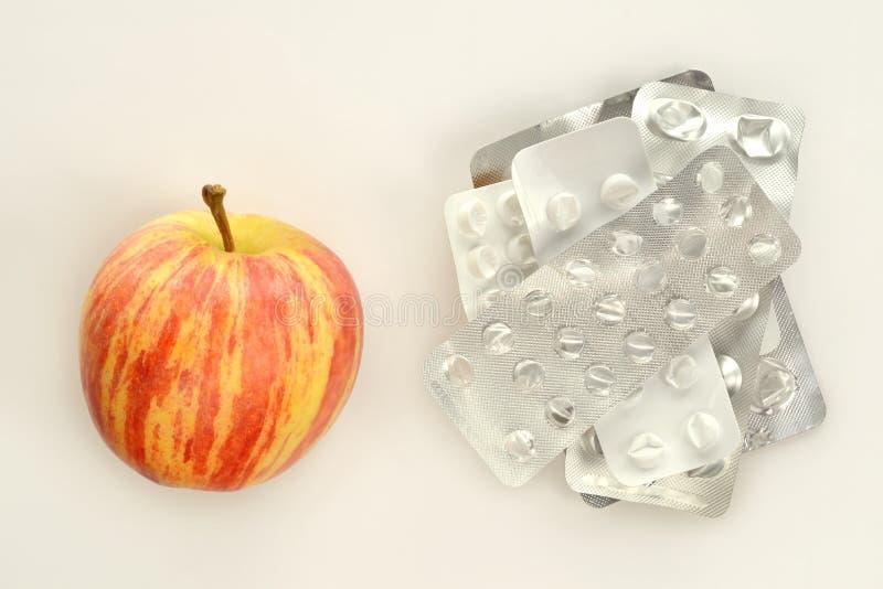 Ένα μήλο εναντίον των κενών φουσκαλών ταμπλετών στοκ φωτογραφία