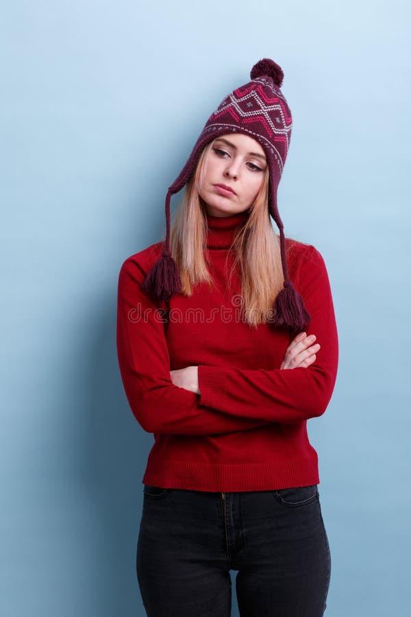 Ένα ματαιωμένο κορίτσι, σε ένα θερμό καπέλο και τα γλυκά, στέκεται cross-legged και κοιτάζει μακριά σκεπτικά πρόσκληση συγχαρητηρ στοκ εικόνες με δικαίωμα ελεύθερης χρήσης