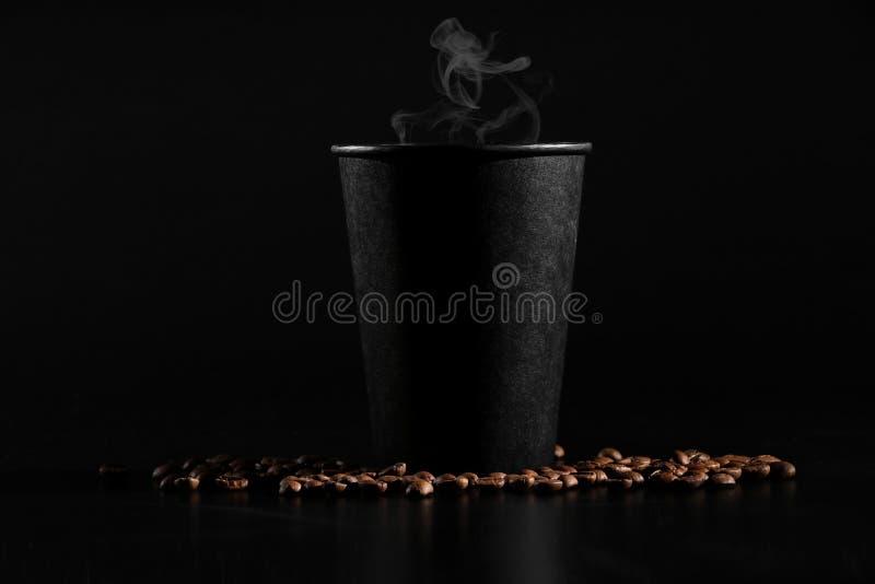 Ένα μαύρο γυαλί με τον καυτό καφέ σε ένα σκοτεινό υπόβαθρο Διεσπαρμένα φασόλια καφέ ευώδης καφές στον πίνακα στοκ εικόνες με δικαίωμα ελεύθερης χρήσης