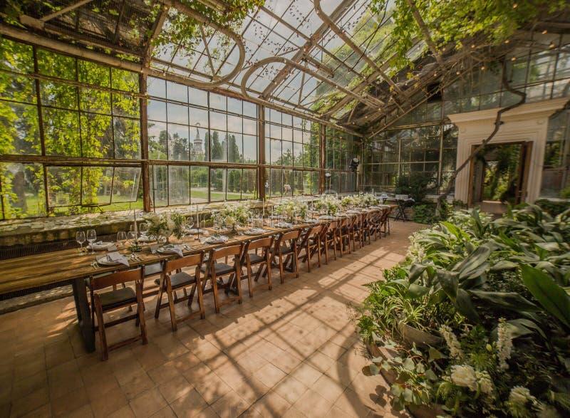 Ένα μεγάλο δωμάτιο γυαλιού με την πρασινάδα σε όλη την περιοχή που διακοσμείται από ένα συμπόσιο σε έναν επικυρωμένο πίνακα με το στοκ εικόνα