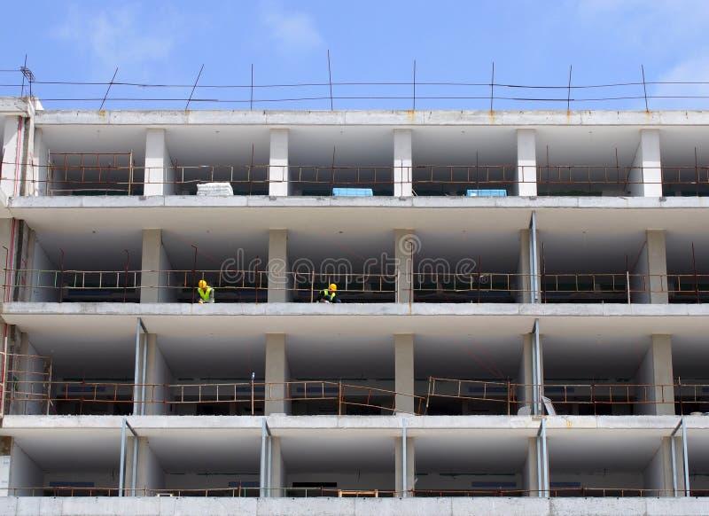 Ένα μεγάλο εργοτάξιο οικοδομής των κατοικημένων διαμερισμάτων με τα άσπρα τσιμεντένια πατώματα και των εργαζομένων στη προστατευτ στοκ εικόνες με δικαίωμα ελεύθερης χρήσης
