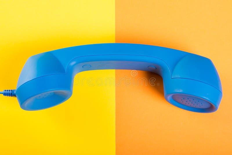 Ένα μεγάλο μπλε ακουστικό τηλεφώνου στο κίτρινο και πορτοκαλί υπόβαθρο στοκ φωτογραφία με δικαίωμα ελεύθερης χρήσης