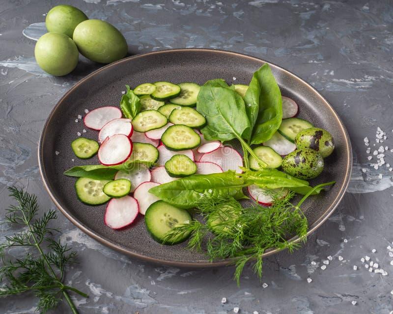 Ένα μεγάλο πιάτο του τεμαχισμένων ραδικιού και του αγγουριού, φρέσκο σπανάκι καρύκεψε με το αλάτι και το πιπέρι Στο υπόβαθρο είνα στοκ φωτογραφίες με δικαίωμα ελεύθερης χρήσης