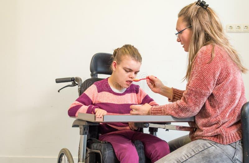 Ένα με ειδικές ανάγκες παιδί σε μια αναπηρική καρέκλα μαζί με έναν εθελοντή εργαζόμενο προσοχής στοκ εικόνες με δικαίωμα ελεύθερης χρήσης