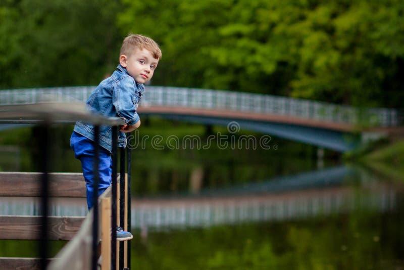 Ένα μικρό αγόρι αναρριχείται σε ένα κιγκλίδωμα γεφυρών στο πάρκο Η απειλή του πνιξίματος Κίνδυνος στα παιδιά στοκ φωτογραφίες με δικαίωμα ελεύθερης χρήσης