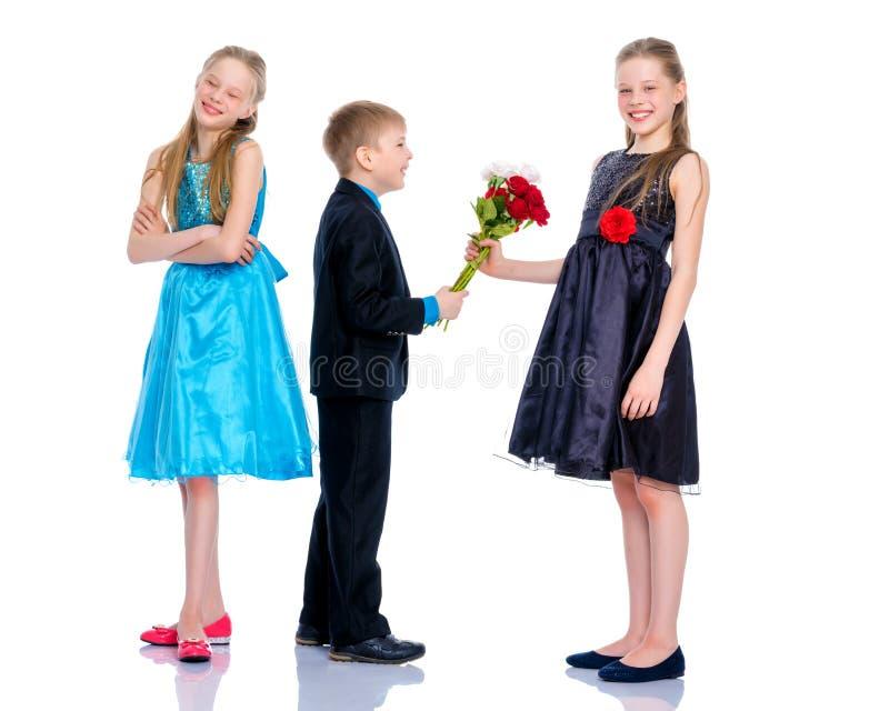 Ένα μικρό αγόρι δίνει τα λουλούδια κοριτσιών στοκ φωτογραφία με δικαίωμα ελεύθερης χρήσης