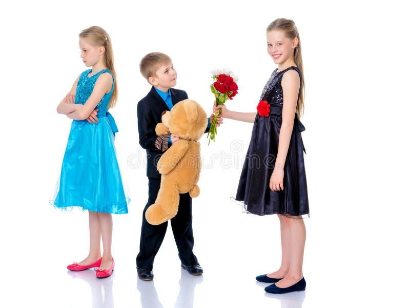 Ένα μικρό αγόρι δίνει τα λουλούδια κοριτσιών στοκ φωτογραφία