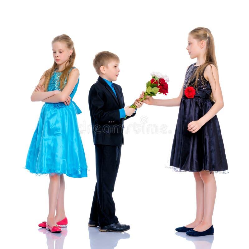 Ένα μικρό αγόρι δίνει τα λουλούδια κοριτσιών στοκ εικόνες