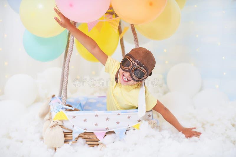 Ένα μικρό αγόρι κάθεται σε ένα καλάθι μπαλονιών στα σύννεφα, που προσποιούνται να ταξιδεψει και να πετάξει με ένα καπέλο αεροπόρω στοκ φωτογραφία με δικαίωμα ελεύθερης χρήσης