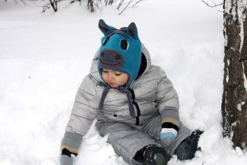 ένα μικρό αγόρι κάθεται στο χιόνι κάτω από ένα δέντρο και κάνει snowflakes σε ένα καπέλο αλόγων στοκ εικόνες