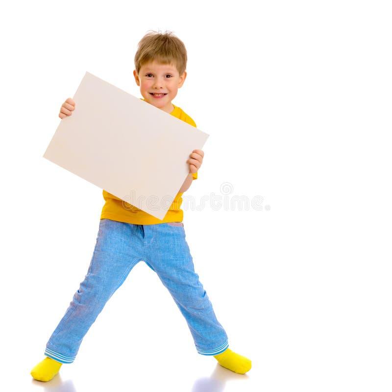 Ένα μικρό αγόρι κοιτάζει από πίσω από ένα κενό έμβλημα στοκ εικόνα