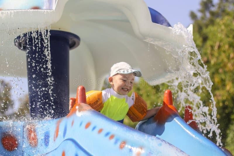Ένα μικρό αγόρι κυλά κάτω μια φωτογραφική διαφάνεια νερού Χαρά παιδιών στο πάρκο νερού Θερινές διακοπές για τα παιδιά στο πάρκο ν στοκ φωτογραφίες