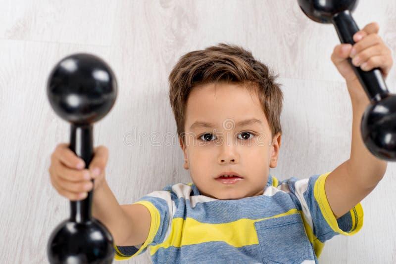 Ένα μικρό αγόρι με τους αλτήρες βρίσκεται στο πάτωμα και κάνει ένα exerci στοκ εικόνα με δικαίωμα ελεύθερης χρήσης