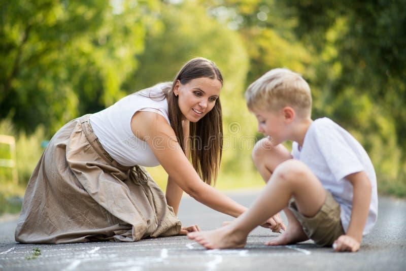 Ένα μικρό αγόρι με το σχέδιο μητέρων hopscotch σε έναν δρόμο στο πάρκο μια θερινή ημέρα στοκ φωτογραφία με δικαίωμα ελεύθερης χρήσης