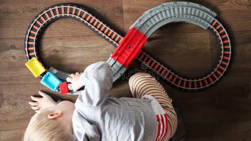 Ένα μικρό αγόρι παίζει έναν σιδηρόδρομο των παιδιών Το Mom προσέχει το γιο της άνωθεν Το παιδί συναρπάζεται με το τραίνο στοκ φωτογραφία