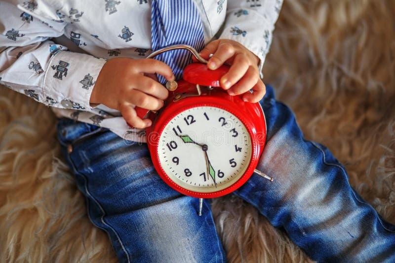 Ένα μικρό αγόρι που κρατά ένα μεγάλο κόκκινο ρολόι περιμένοντας τα θαύματα στοκ φωτογραφία με δικαίωμα ελεύθερης χρήσης