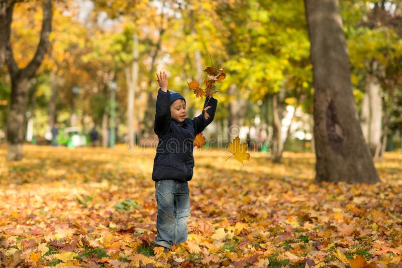 Ένα μικρό αγόρι που φορά τα τζιν και μια μπλε ζακέτα ρίχνει χαρωπά το YE στοκ φωτογραφίες