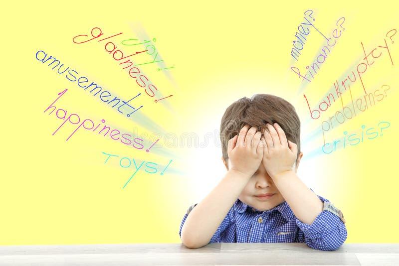 Ένα μικρό αγόρι σε ένα απομονωμένο υπόβαθρο κάθεται και σκέφτεται για τα ακατανόητα προβλήματα των ενηλίκων και των κατανοητών πα στοκ φωτογραφία